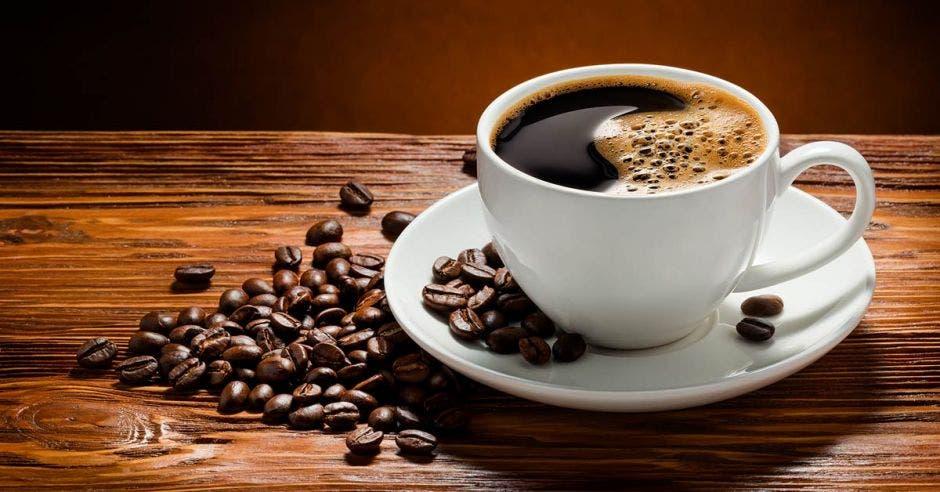 taza de café y granos de café sobre mesa de madera