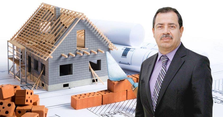 un hombre de bigote y traje sobre la imagen de una casa en construcción