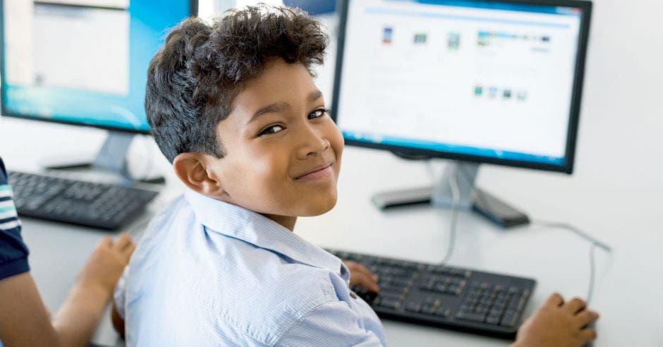 Joven de colegio utilizando una computadora.