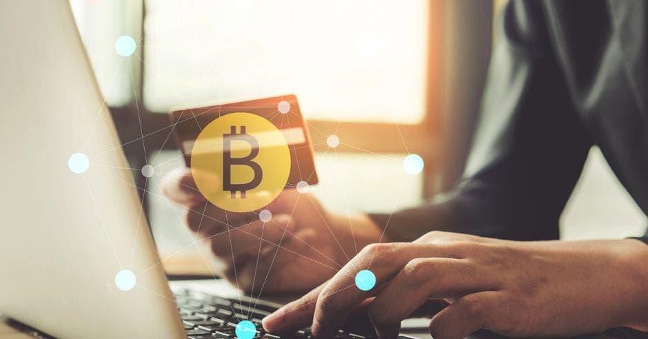 hombre usando laptop con una tarjeta de crédito y el símbolo de Bitcoin en una mano