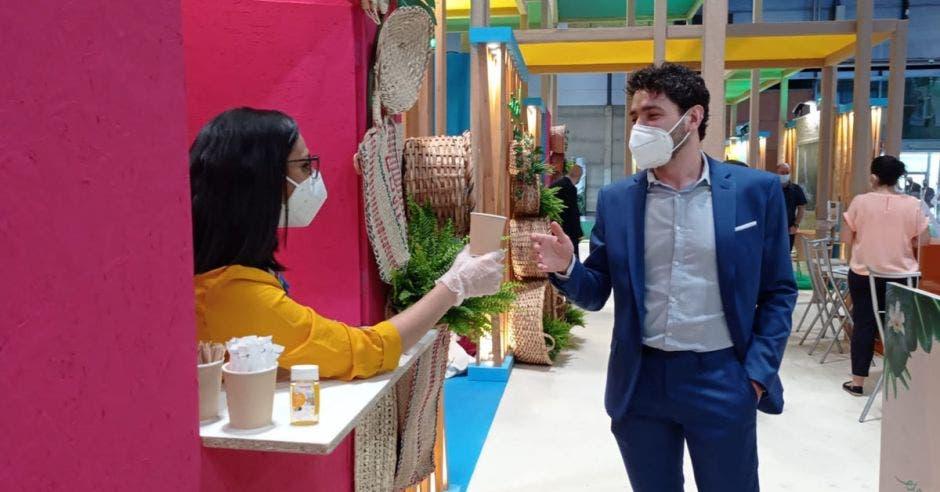 una mujer sirve un café a un hombre que pasa frente a un stand de exposición