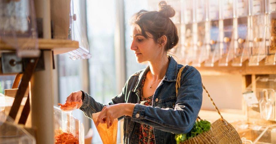 joven comprando en una tienda de comida a granel. Ella compra pasta orgánica