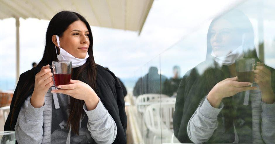 Una mujer tomando café y con una mascarilla mal puesta