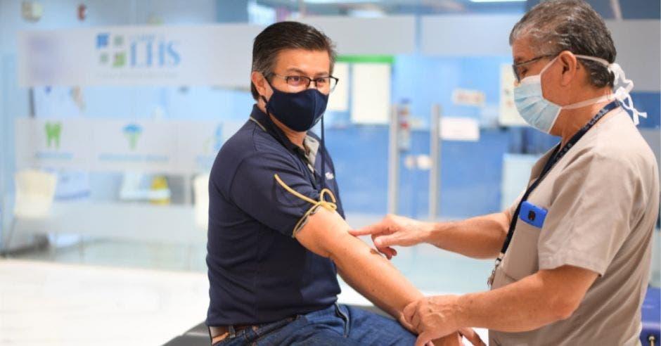 médico sacando muestra de sangre a hombre adulto