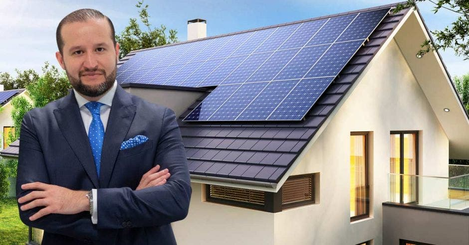 un hombre de saco azul y corbata azul sobre el fondo de una casa con paneles solares