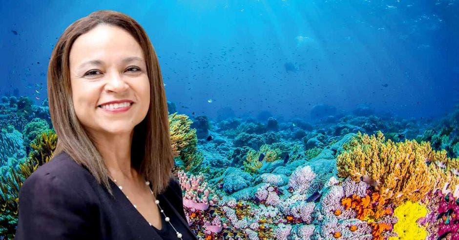 una mujer de pelo lacio sobre un fondo marino con muchos corales. Concepto de protección del mar.