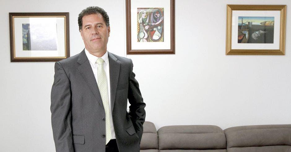 Hombre de traje frente a sillón y cuadros