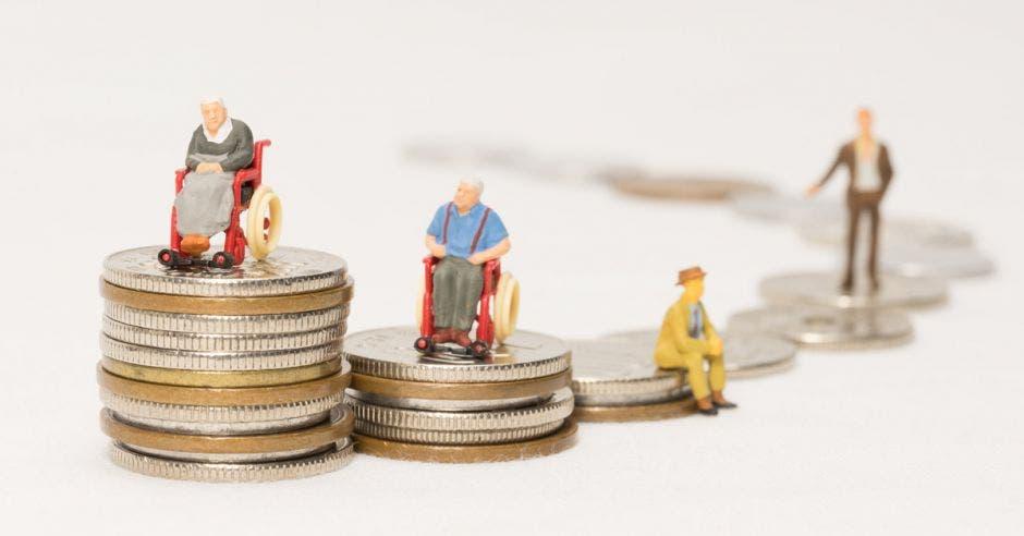 torres de monedas, de diferentes tamaños, con figurillas de personas de la tercera edad encima