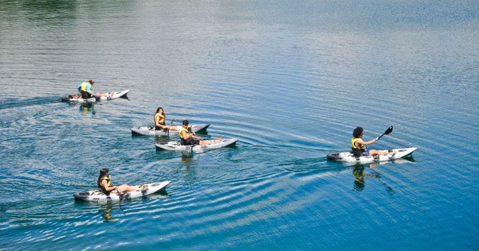 un grupo de personas recorre una laguna en kayak