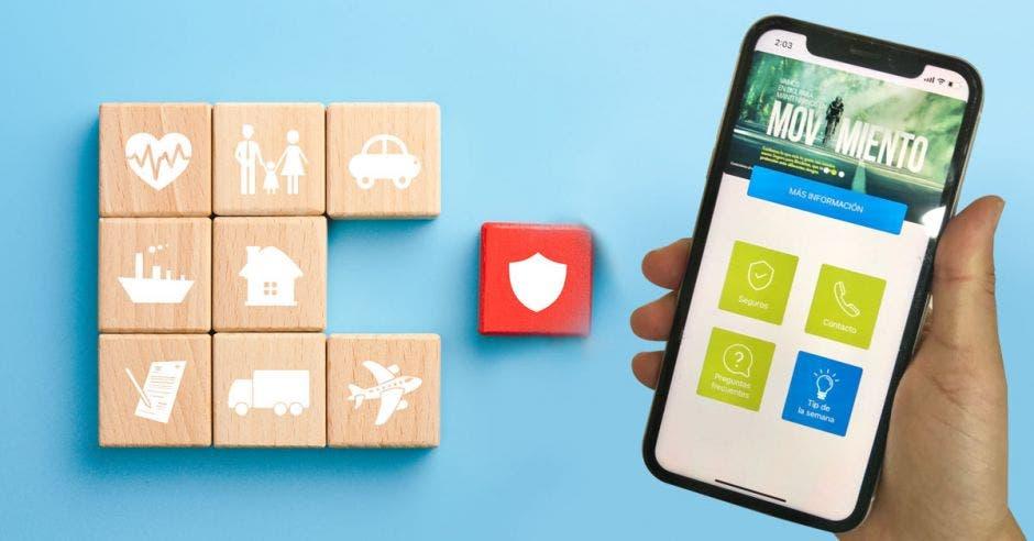 cubos de madera con distintos símbolos junto a mano sosteniendo celular con la app de BN Seguros