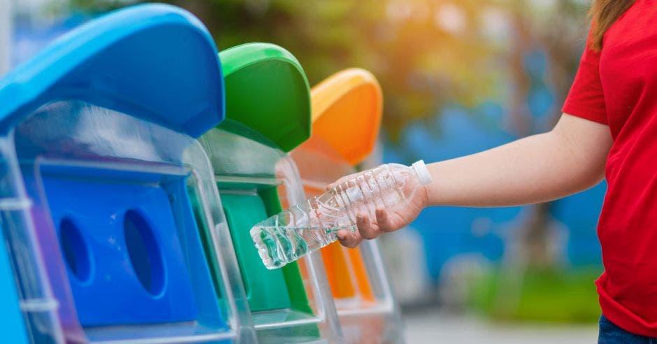 Mano de mujer de primer plano lanzando una botella de agua de plástico vacía a la papelera de reciclaje, concepto de protección del medio ambiente