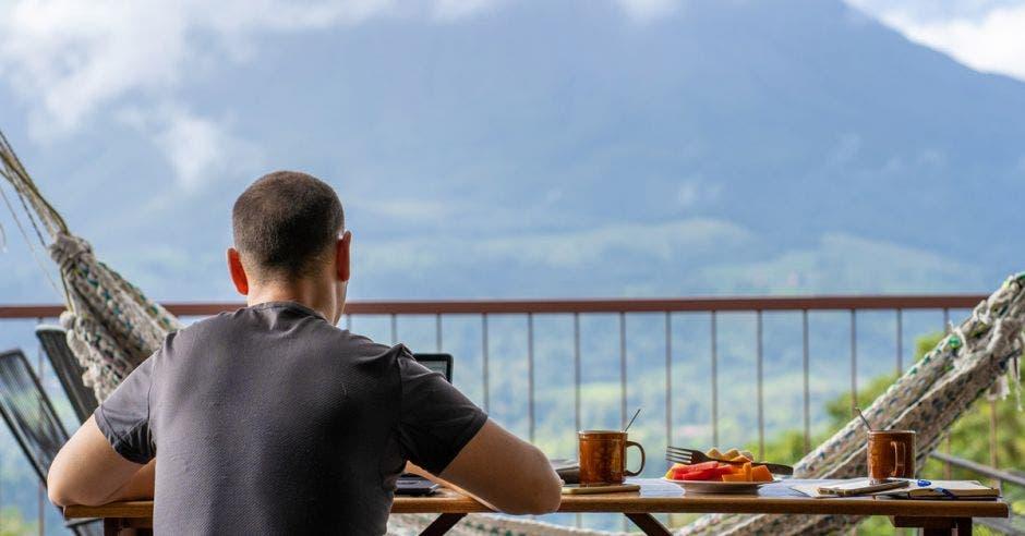 un hombre disfruta su desayuno en hotel con vista al mar