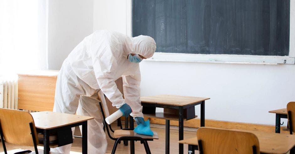 Una persona limpiando y sanitizando un aula