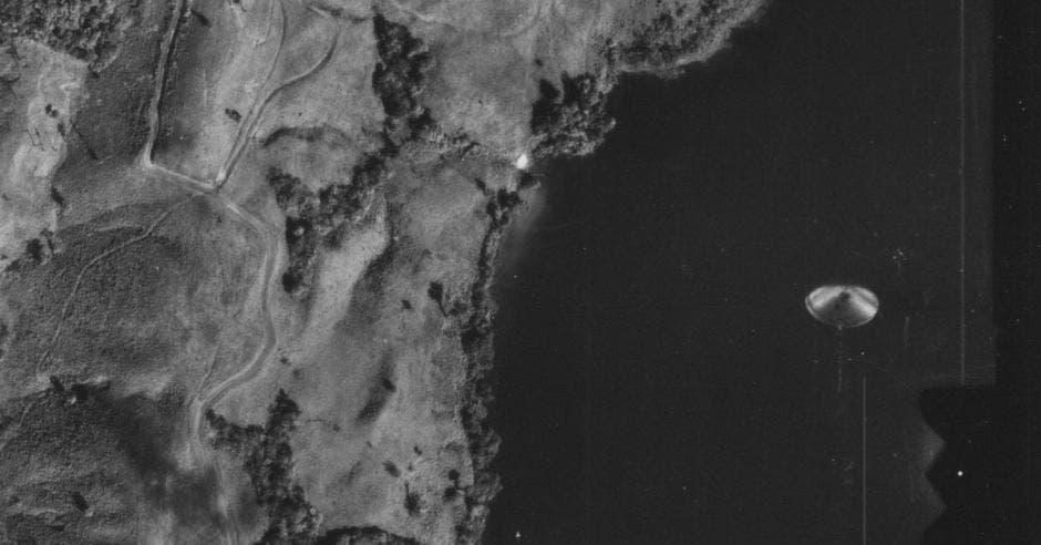 un disco metálico recortado sobre una laguna amplia. Foto en blanco y negro.