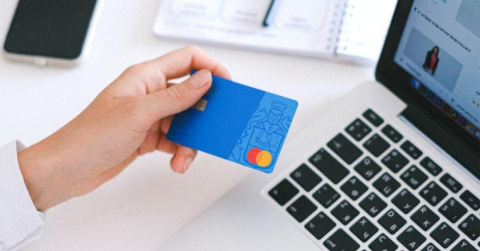 mujer sosteniendo tarjeta para hacer pago electrónico