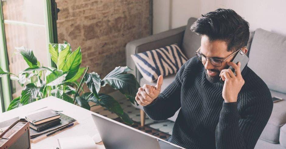 Hombre sentado en una mesa de madera con ordenador portátil y teléfono móvil. Fondo borroso