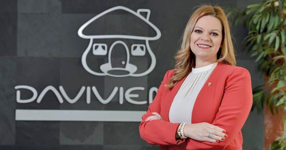 Mujer de rojo frente a logo de Davivienda