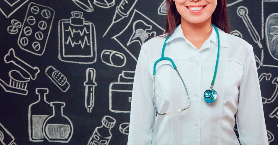 Una mujer con uniforme de medicina y al fondo dibujos de medicina