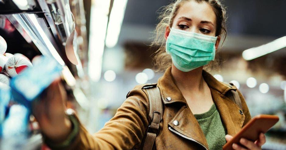 Joven con mascarilla usando teléfono móvil y comprando comestibles en el supermercado durante la pandemia de virus covid-19