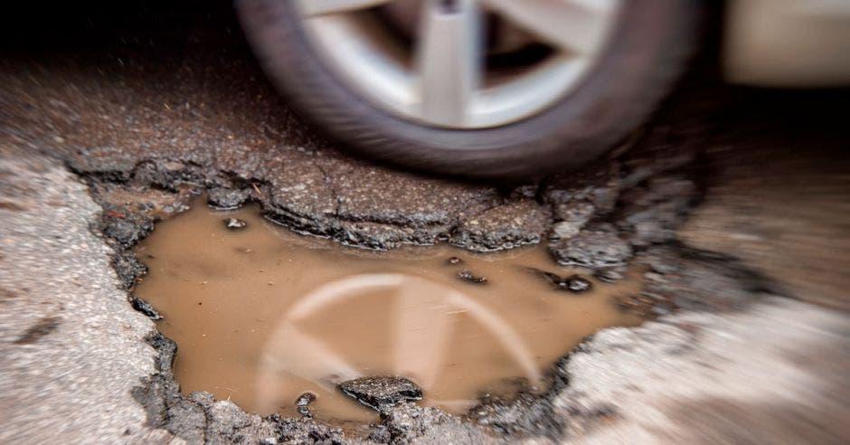 un gran hueco en la carretera lleno de agua sucia