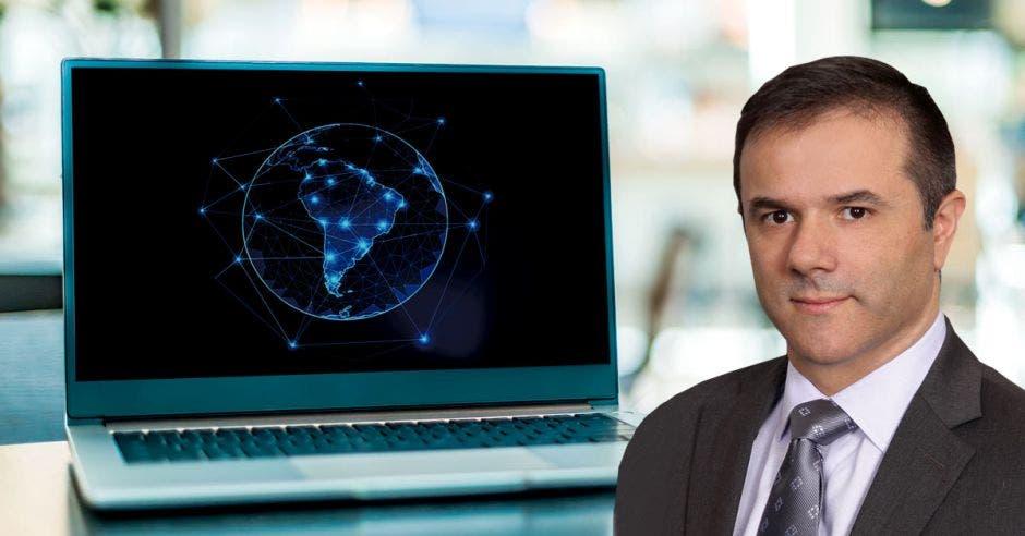 un hombre de saco y corbata sobre un fondo de una computadora con el mapa de latinoamérica