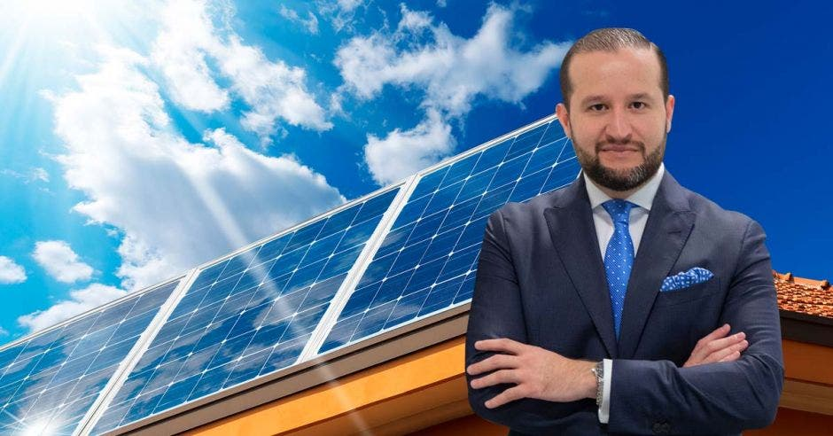 un hombre de barba, saco y corbata sobre un fondo de paneles solares