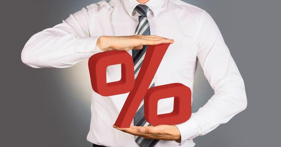 Persona sostiene símbolo de porcentaje en rojo