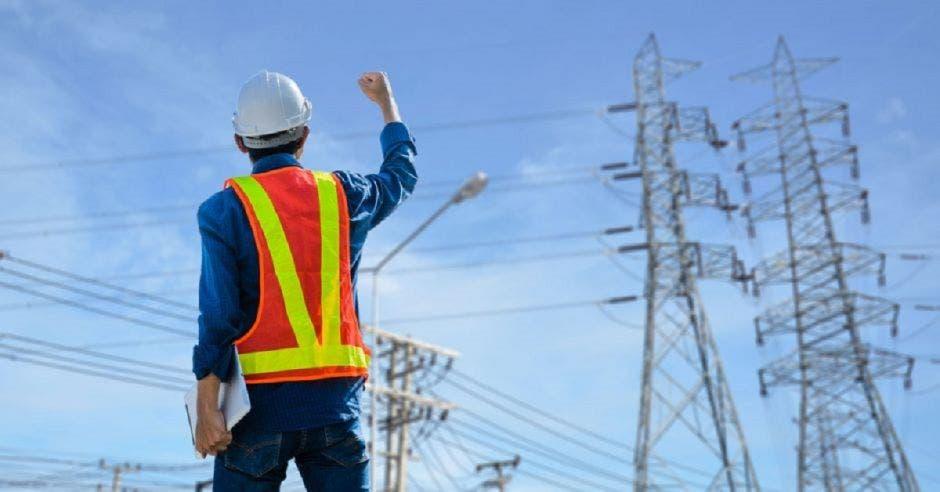Trabajador eléctrico frente a una torre de distribución