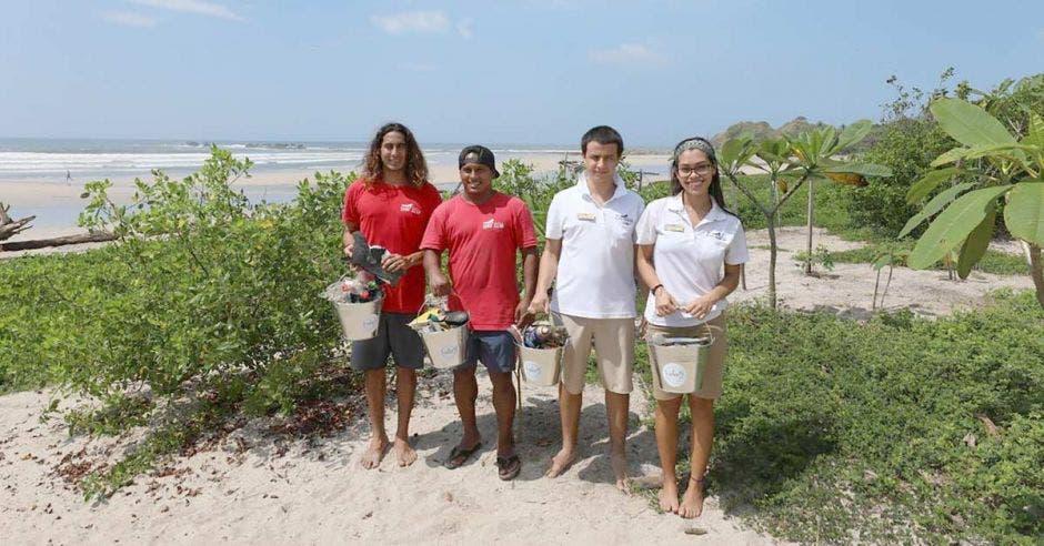 dos hombres de camisa roja, un hombre da camisa blanca y una mujer de camisa blanca posan con baldes de aluminio en una playa
