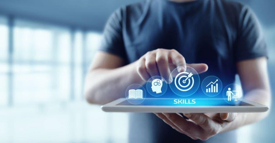 hombre sosteniendo tablet con dibujos de tecnología y la palabra Skills