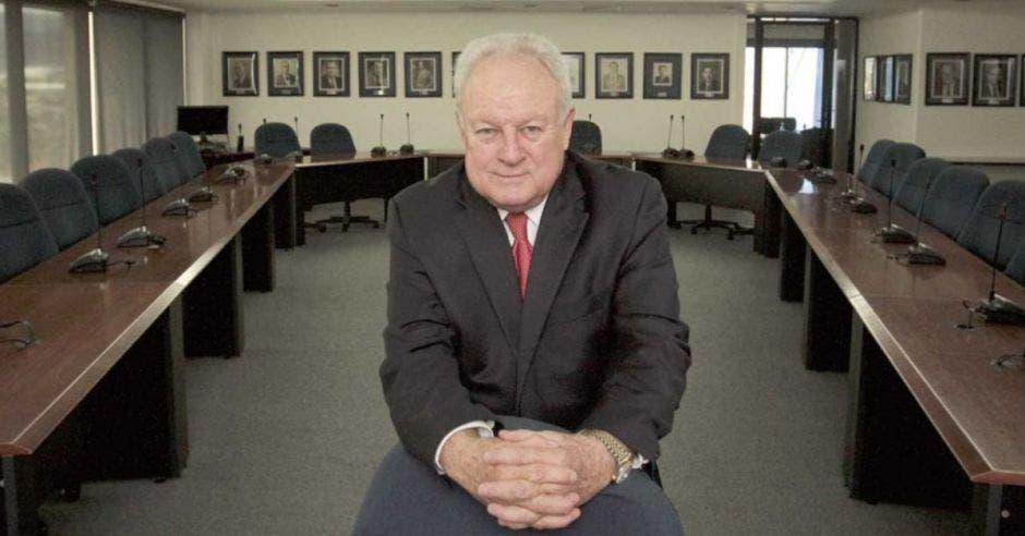 Hombre de traje en oficina, apoyado en una silla
