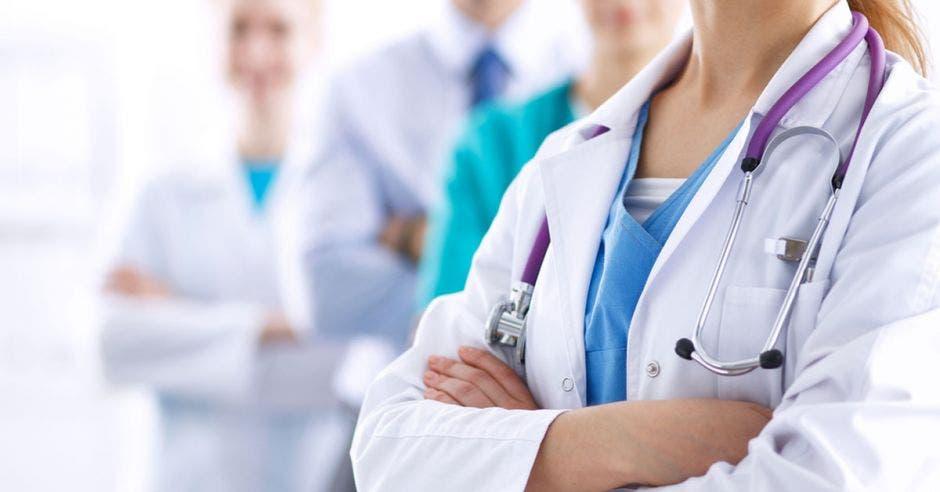 Fila de médicos con bata blanca y brazos cruzados