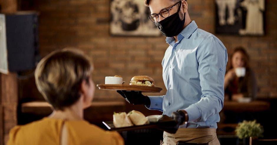 un hombre con mascarilla sirve el almuerzo a un comensal en un restaurante