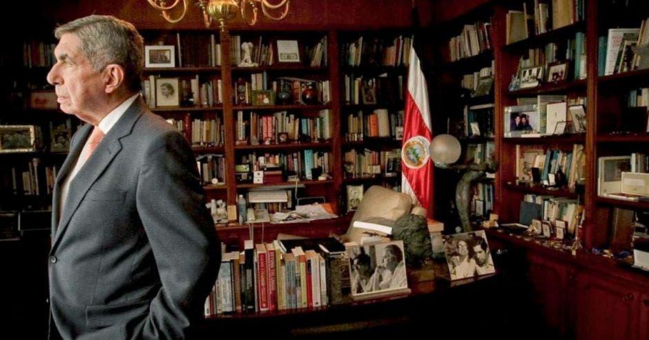 +Óscar Arias de pie en su biblioteca