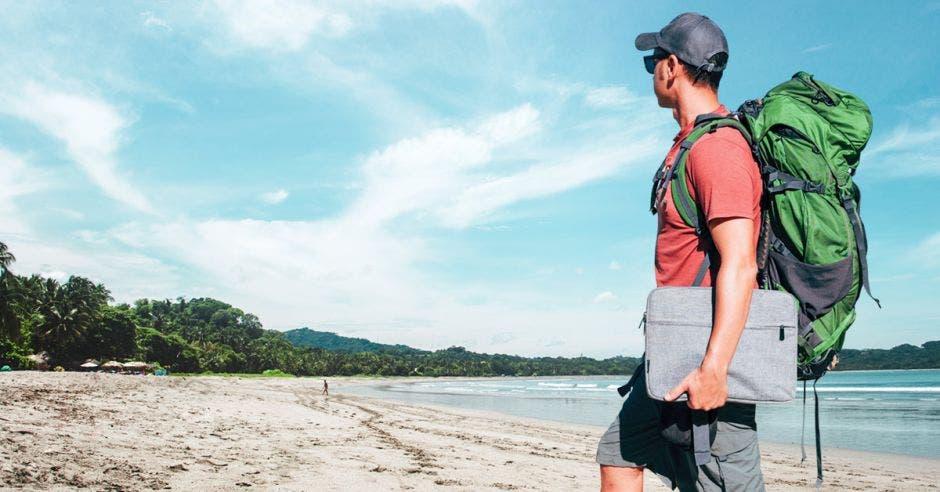 un hombre con varias maletas de viaje sobre una playa