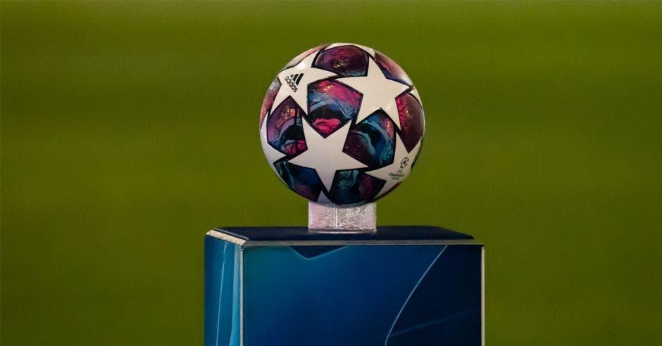 un balón con múltiples estrellas colocado sobre un atril en el centro de una campo de fútbol