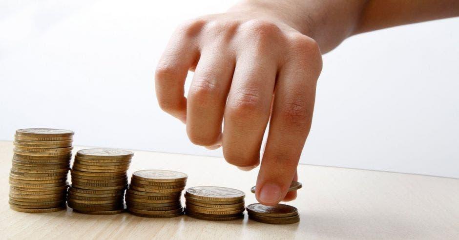 Mano de persona sobre fila de monedas