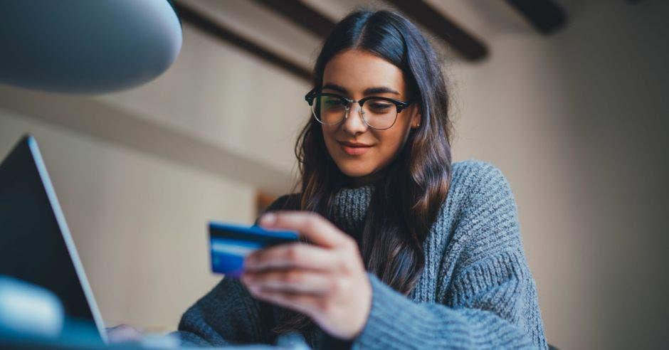 Joven hermosa mujer trabajando en casa con tarjeta de crédito y usando computadora portátil