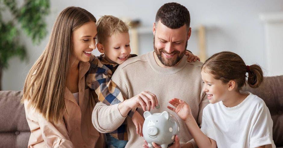 papás e hijos pequeños sonriendo y ahorrando en alcancía de cerdito