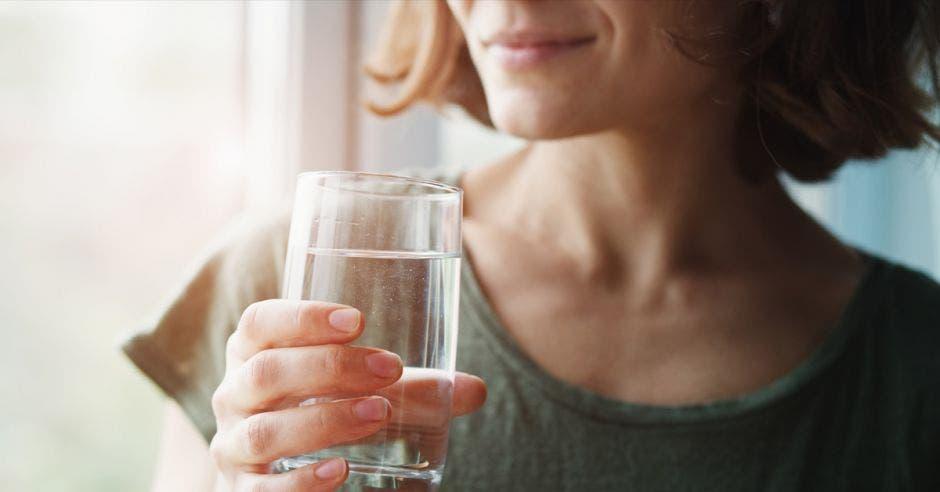 mujer joven saludable sosteniendo un vaso de agua