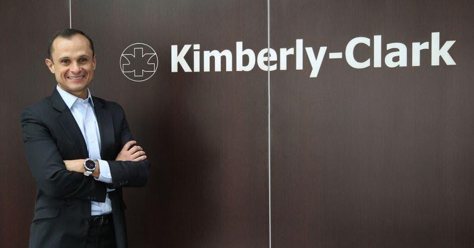 un hombre de traje sobre un fondo café que dice kimberly clark