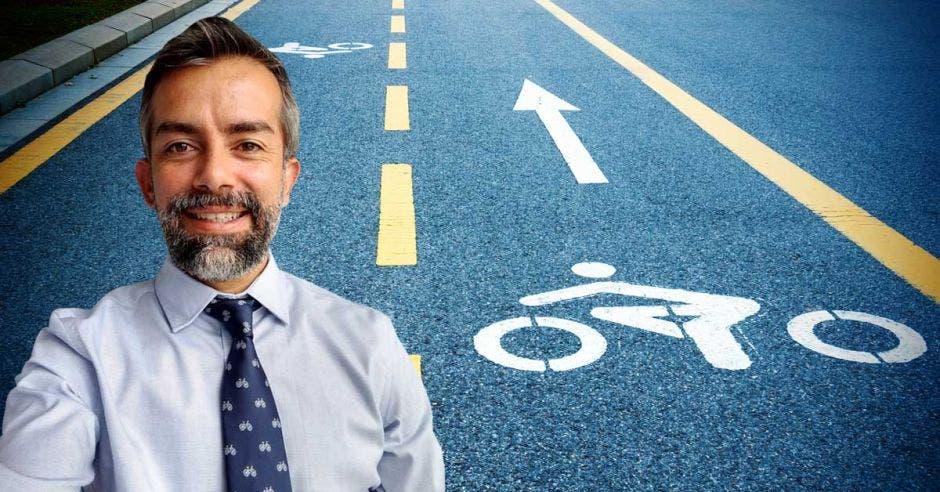 un hombre de corbata y barba sobre el fondo de una ciclovía