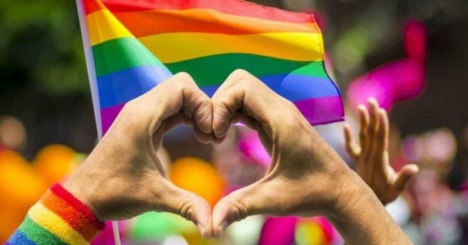 la bandera gay y unas manos haciendo un corazón