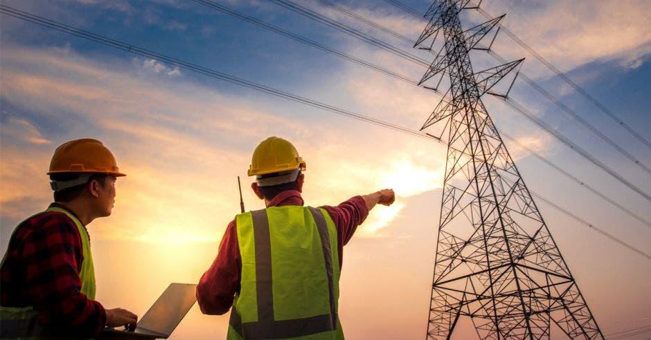 Dos técnicos bajo una torre de distribución eléctrica
