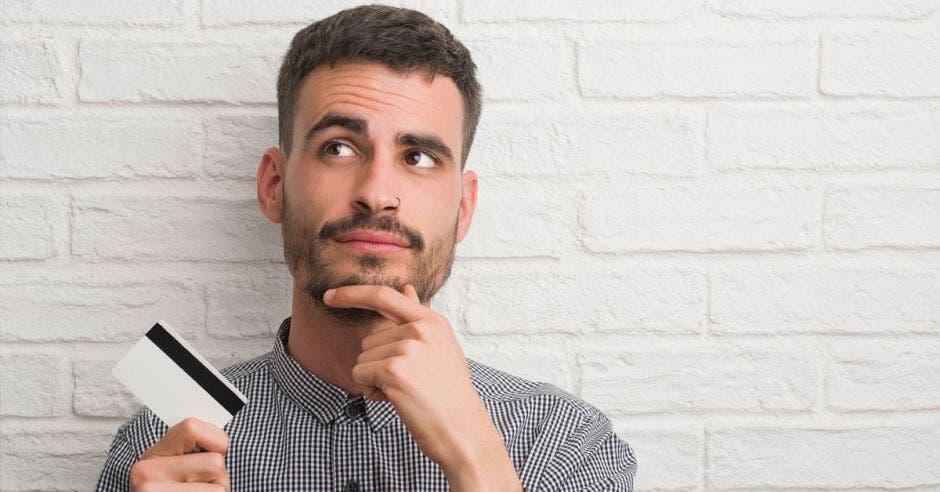 hombre joven con barba y bigote, sosteniendo una tarjeta de crédito y la otra mano tocando su barbilla, con expresión de duda en su cara