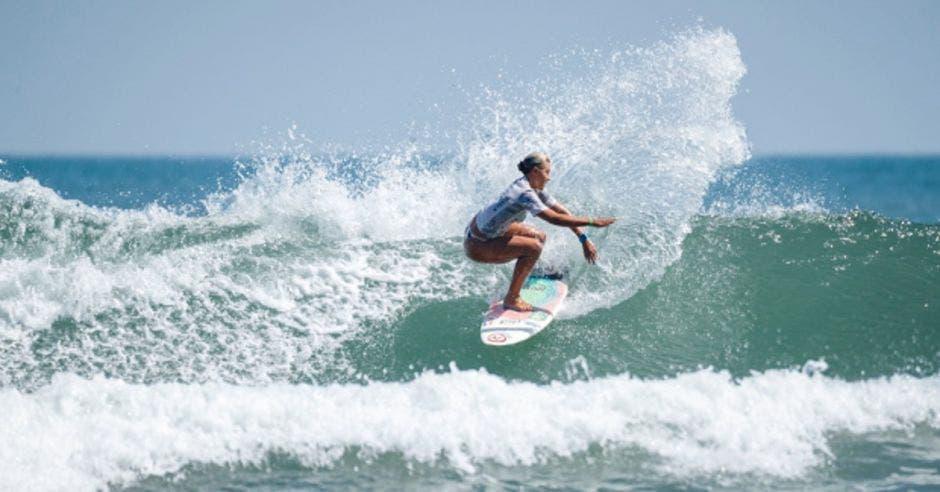Mujer en tabla de surf en ola
