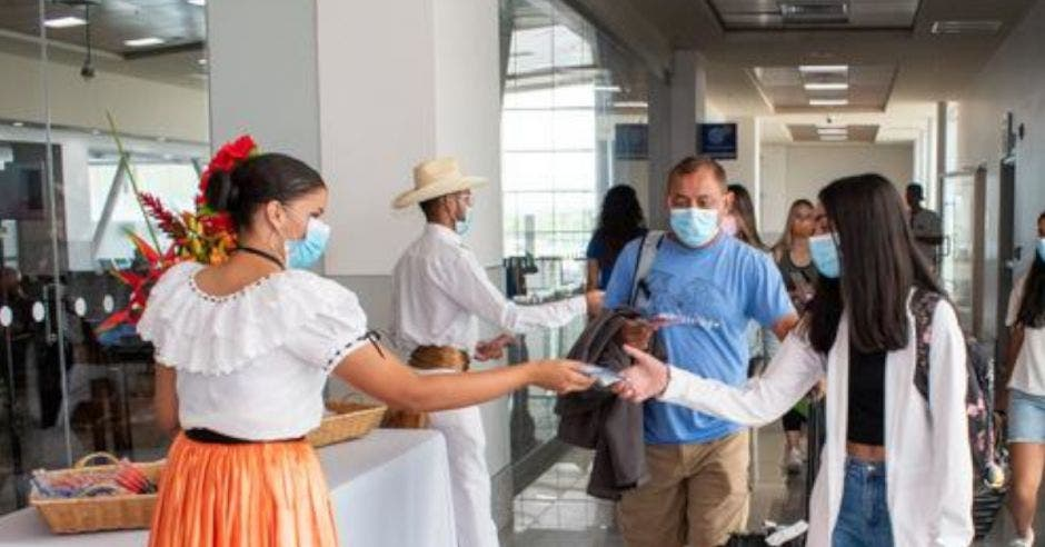 personas recibiendo a turistas en aeropuerto de Guanacaste