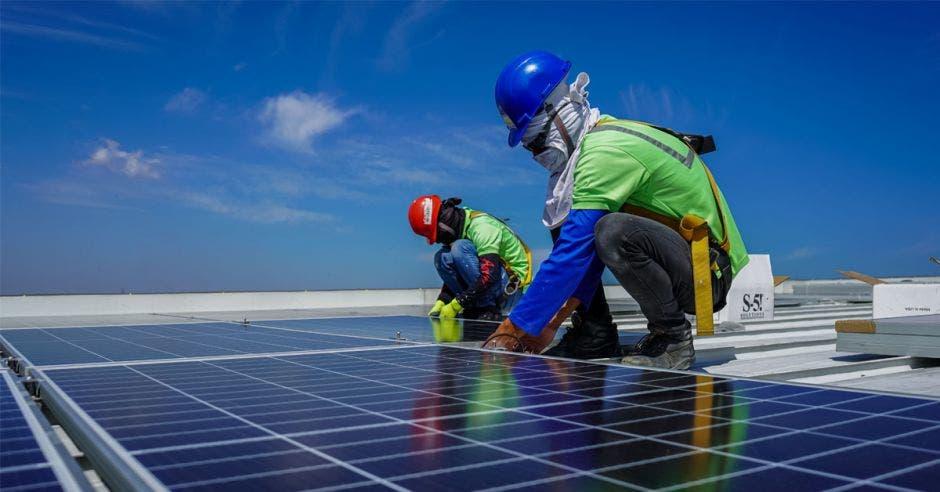 dos hombres sobre un techo instalando paneles solares
