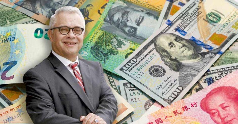 Hombre de traje frente a billetes internacionales