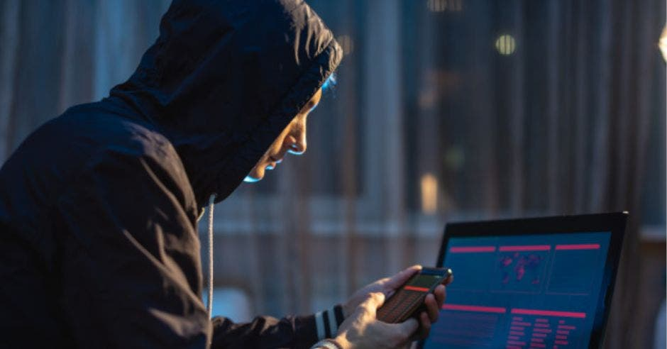 hombre con sudadera con capucha sosteniendo celular frente a una laptop